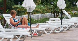 Beautiful mature woman sitting near pool stock video