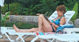 Beautiful mature woman sitting near pool stock video footage