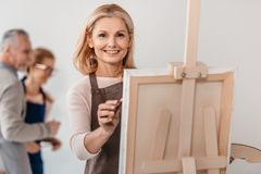 Beautiful mature woman smiling at camera while painting on easel at art. Class stock image