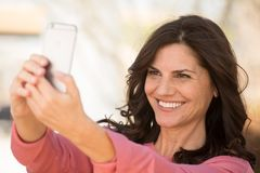 Beautiful mature woman smiling. Selective focus of a beautiful mature woman smiling outside Stock Photography
