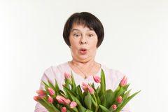 The beautiful mature woman. Is surprised to a bouquet of tulips Stock Image