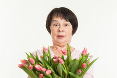 The beautiful mature woman. Is surprised to a bouquet of tulips Royalty Free Stock Photography