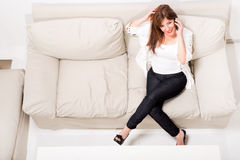 A beautiful mature woman talking on her cell phone on the sofa Royalty Free Stock Photo