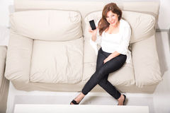 A beautiful mature woman talking on her cell phone on the sofa Royalty Free Stock Photos