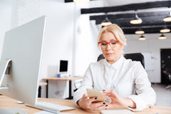 Beautiful mature woman using smart phone. In the office Stock Images