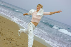 Beautiful mature women running on a beach Royalty Free Stock Image