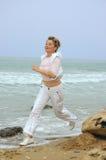 Beautiful mature women running on a beach stock image