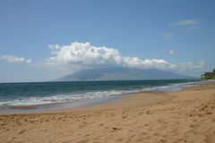 Maui, Hawaii beach with the West Maui MTs in the background. Kaavakapu Beach, with it`s blue waters,on a beautiful sunny day with white billowy clouds hanging Stock Photo