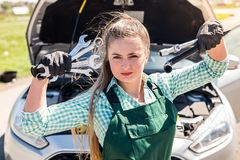 Beautiful mechanic posing with different tools before car stock photo