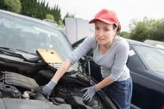 Beautiful mechanic woman working on car Stock Photos