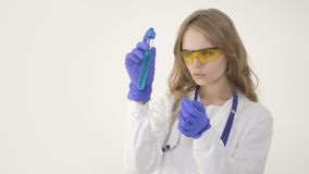 Beautiful medical doctor in protective glasses is working with a test tube. On white background stock footage