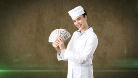 Beautiful medical woman doctor in uniform. Studio painted background. Concept of profitable health care. Stock Image