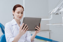 Beautiful medical worker looking at the tablet. Positive emotions. Smiling female person holding her gadget in both hands and sitting in dentist cabinet while stock photos