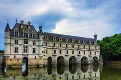 View of Chateau de Chenonceau and river. Beautiful medieval castle Chateau de Chenonceau in France and river flowing in its arches royalty free stock photos