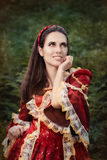 Beautiful Medieval Princess Smiling. Portrait of a happy beautiful Renaissance queen in red royal dress stock images