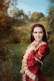 Beautiful Medieval Princess Smiling. Portrait of a happy beautiful Renaissance queen in red royal dress royalty free stock image