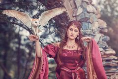 Beautiful medieval woman with a flying owl on her hand. Beautiful medieval woman, sorceress, with a flying owl on her hand. Amazing scene near ancient stone arc stock image