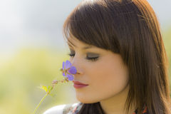 Beautiful meditative girl sniffing a flower. The young woman enjoys the beauty of nature. Wonderful picture with nice colors Royalty Free Stock Photo