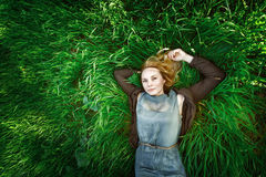 Beautiful meditative young woman lying in the grass. Summer. Royalty Free Stock Photos