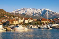 Beautiful Mediterranean landscape on sunny winter day. Fishing boats in harbor at foot of snowy mountains. Montenegro, Tivat royalty free stock photography