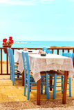 Beautiful Mediterranean restaurant at sea side. Two wooden tables and chairs in front of the sea shore Stock Photos