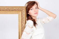 Beautiful melancholic woman in dress stands near frame Stock Photos