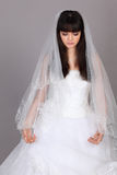 Beautiful melancholy look down. Beautiful melancholy bride dressed in white dress look down on gray background stock photography