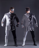Beautiful men posing in masquerade costumes Stock Images