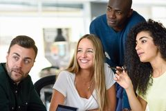 Beautiful men and women working toghether wearing casual clothe. Four young people working together. Beautiful men and women in a business meeting wearing casual Stock Images