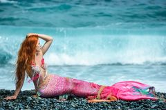 Beautiful mermaid on sea shore