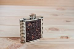 Beautiful metal flask for alcoholic drinks with drawings in Egyptian style on a wooden background.  Royalty Free Stock Image