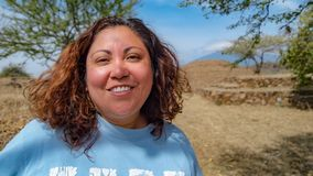 Beautiful Mexican woman in front of a archaeological site with Aztec piramide stock image