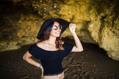 Beautiful mexican woman with hat and sunglasses sunbathing on rocks beach on summer vocation time Stock Photos