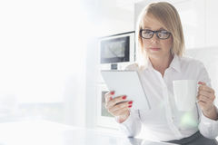 Beautiful mid adult businesswoman having coffee while using table PC at home Royalty Free Stock Photo