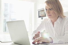 Beautiful mid adult businesswoman using laptop while having coffee at home Royalty Free Stock Images