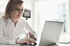 Beautiful mid adult businesswoman using laptop while having coffee at home Royalty Free Stock Photography