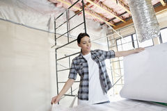 Beautiful mid adult contractor looking at building plans at construction site Stock Photos