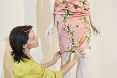Beautiful mid adult woman adjusting dress on mannequin in fashion store Royalty Free Stock Photography
