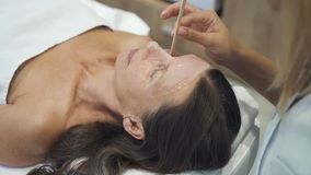 Beautiful middle age woman getting face mask at spa stock video