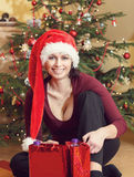 Beautiful middle age woman in santa hat sitting near the Christmas tree Royalty Free Stock Photos
