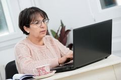 Beautiful middle age woman using laptop in home Royalty Free Stock Images