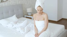 Beautiful middle aged blonde woman wrapped in towel white towel walking stock video