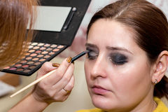 Beautiful middle-aged model, which is applied eyeshadow. Royalty Free Stock Photography