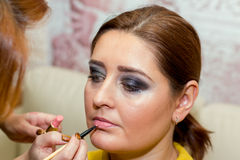 Beautiful middle-aged model, which is applied makeup. Royalty Free Stock Image