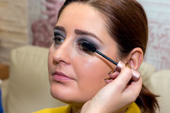 Beautiful middle-aged model, which is applied mascara. Stock Images