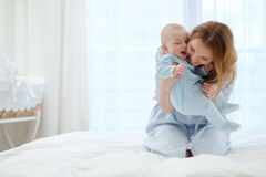 Happy middle aged mother with her child in a bed royalty free stock photography