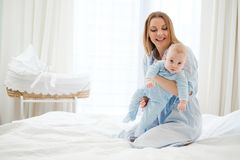 Happy middle aged mother with her child in a bed stock photo