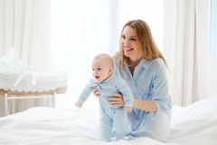 Happy middle aged mother with her child in a bed stock image