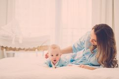 Happy middle aged mother with her child in a bed. Beautiful middle aged mother with her child in a bed royalty free stock image