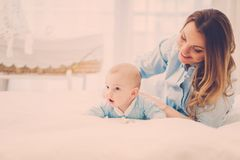 Happy middle aged mother with her child in a bed. Beautiful middle aged mother with her child in a bed stock image